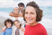 Woman smiling with her family on the beach (thumbnail)