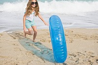 Girl rolling an inflatable ring on the beach