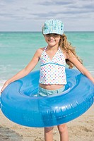 Girl wearing an inflatable ring on the beach