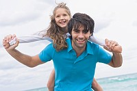 Man giving his daughter piggyback on the beach