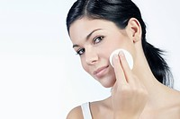 Young woman looking towards the viewer while removing make_up with a cotton pad, beauty