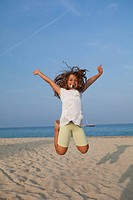 Happy girl jumping high on the beach