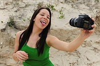 Women with a digital SLR camera takes a picture of herself on the beach