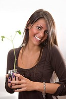Young woman in her 20s holding pot with plant