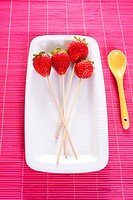 Strawberry sticks in squared dish with yellow spoon on the side