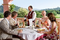 Waiter presenting wine to well_dressed couples at table on restaurant balcony