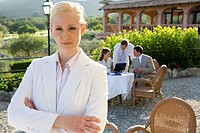 Confident businesswoman with arms crossed at cafŽ with coworkers in background