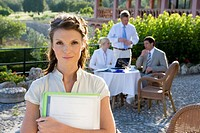 Confident businesswoman holding paperwork at cafŽ with coworkers in background