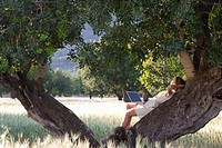 Woman with laptop laying in tree