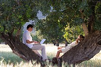 Couple with laptop laying against tree