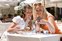 Women looking down at cell phone at sunny, outdoor cafŽ