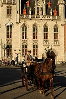 Carriage with tourists on the Grote Markt square with Provinciaal Hof Provincial Court building in the historic center of Bruges, Belgium, Europe