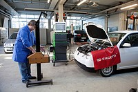 Master Craftsman of motor vehicle mechanics controlling the headlight setting of a car in a workshop