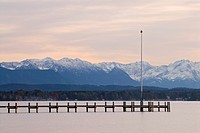 A pier reaching into Lake Starnberg with the Bavarian Alps in the back, near Ambach, Bavaria, Germany, Europe
