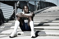 Dark-skinned athlete sitting on a bridge