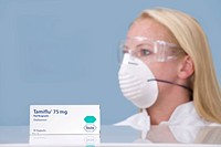 Pharmacist with protective mask and the drug Tamiflu