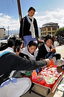 Schoolgirls admiring glass beads of a merchant selling wares on the street, Leh, Ladakh, India, Himalayas, Asia