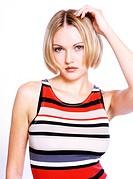 blond woman wearing fasciated t_shirt, haelt eine Hand an ihren Kopf, schaut in die Kamera.