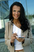 young dark_haired woman wearing suit using palmtop, looks into the camera and smiles