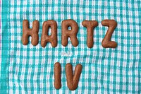 Hartz IV, written with Russian bread letter biscuits on an old teatowel