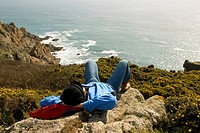 Woman lying on a rock, taking a break, hiking, coast, sea, Cornwall, southern coast, South England, Great Britain