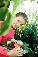 young woman with fresh fruits in garden