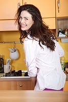 woman with nightshirt drinking milk in the kitchen