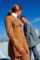 young blond woman wearing beige suit passin by a man wearing grey suit, with lightly cloudy sky in background