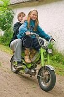 Girl and boy on a moped, girl driving