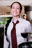 portrait of young waitress serving wine
