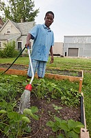Detroit, Michigan - A boy waters a garden tended by children ages 5-11 in a program called Growing Healthy Kids  The program is part of the Earthworks...
