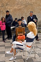 Portrait artist and spectators on Piazza IX Aprile, Taormina, Sicily, Italy