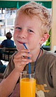 A boy, 5 years, drinking orange juice with a straw