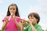 Young boy and girl playing the recorder.