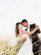bride and groom dancing on beach