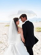 bride and groom walking under parasol