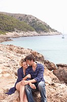 couple sitting on rocks at beach