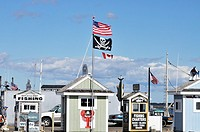 Deep sea, sport and charter fishing ticket booths on the waterfront with the American and Canadian flags flying on a sunny summer´s day, Plymouth Harb...