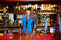 Bartender posing in british pub interior.