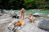 Children and a dog at a campfire on the banks of Brandenberger Ache River, North Tyrol, Austria, Europe
