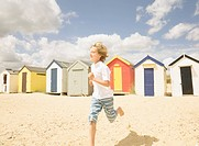 Boy running in front of beach huts