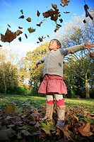 girl tossing autumn foliage
