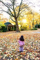 autumnal mood at a park, little girl walking to the sun