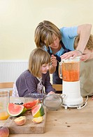 boy, girl and mum making fruit smoothies