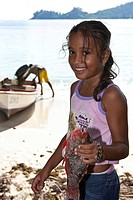 Young Creole girl, about 9 years old, holding freshly caught parrot fish, Baie Lazare, Mahe Island, Seychelles, Indian Ocean, Africa