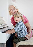 Granny and grandson sit at a piano