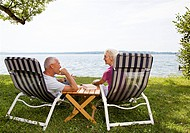 senior man and woman in deck chairs