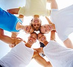 Upward view of a happy group in a huddle