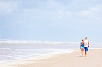 Couple strolling barefoot on the beach