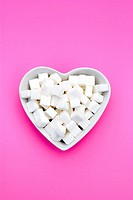 White heart-shaped bowl filled with sugar cubes on pink